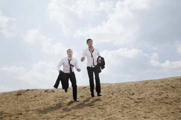 Two young businessmen running and exhausted in the desert, holding jackets