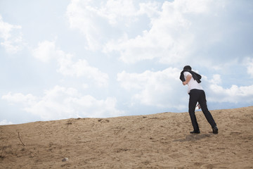 Young businessman lost and walking through the desert