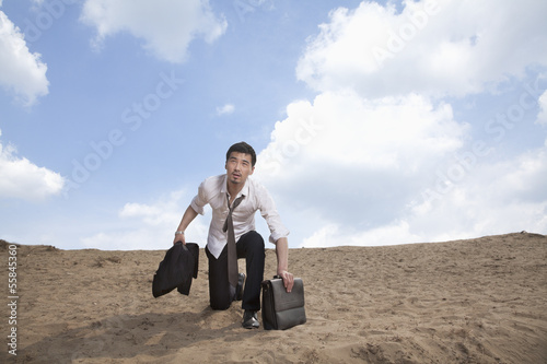 Young businessman kneeling in the desert and holding a briefcase, exhausted
