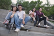 Two young couples sitting and resting on concrete steps outside with skateboards and roller blades
