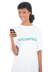 Charming black haired volunteer texting with her mobile phone