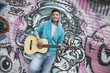 Young smiling street musician leaning on a wall with graffiti drawings and playing his guitar