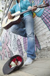 Young street musician playing guitar and busking for money in front of a wall with graffiti