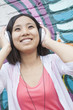 Young smiling woman holding her headphones while enjoying listening to music in front of wall with graffiti