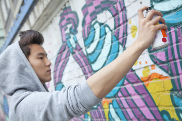 Serious young man concentrating while holding a spray can and spray painting on a wall outdoors