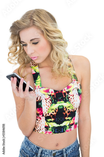 Thinking retro blonde model looking at her mobile phone