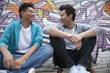 Two young men sitting on their skateboards and hanging out in front of a wall with graffiti