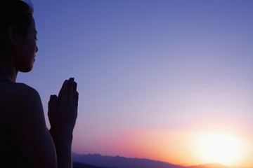 Serene young woman with hands together in prayer pose  in the desert in China, silhouette, sun setting
