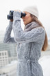 Gorgeous woman with winter clothes on looking through binoculars
