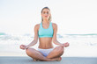 Relaxed slender blonde in sportswear meditating