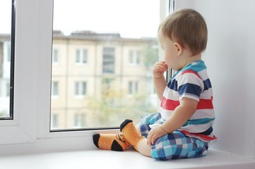 baby looks out of window