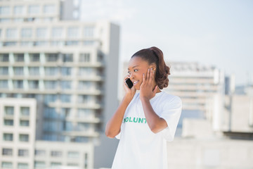 Cheerful altruist woman on the phone covering her ear