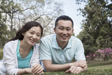 Portrait of couple lying in grass in park.