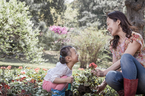 Mother and daughter planting flowers.