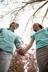 Happy smiling young couple holding hands in the park in springtime, low angle view