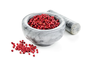 Pink pepper with mortar and pestle on white background