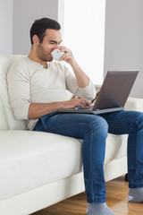 Relaxed attractive man drinking coffee while working on his lapt