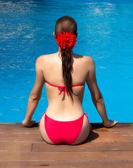 Beauty Brunette Girl Sitting on edge of Swimming Pool