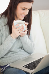 Relaxed girl sitting on a sofa holding a cup of coffee and looki