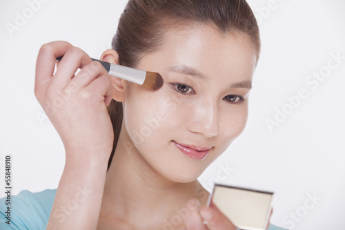 Young beautiful woman looking into a mirror and applying make up with a make up brush, studio shot