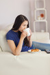 Woman sitting on the sofa drinking coffee with a pastry