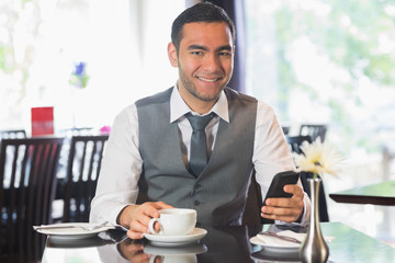 Businessman in a restaurant holding phone