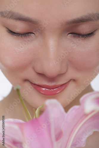 Close -Up of young beautiful woman smelling a  large pink flower, studio shot