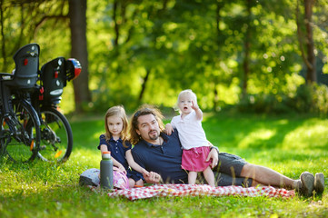 Father and his daughters picnicking in the park