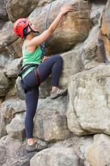 Pretty girl climbing rock face