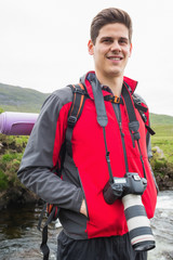 Happy man on a hike with a camera around his neck