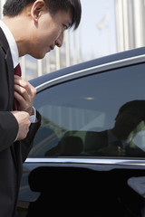 Businessmen straightening tie using reflection in car window.