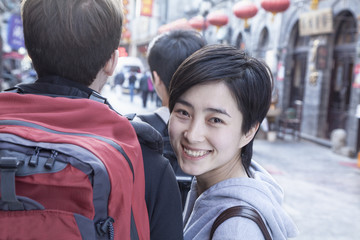 Young couple walking down street, woman looking over shoulder.