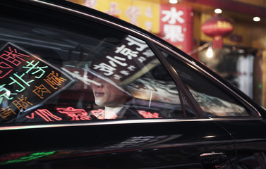 Two business people sitting in the back of a car driving through the city at night, reflections of store signs on the car