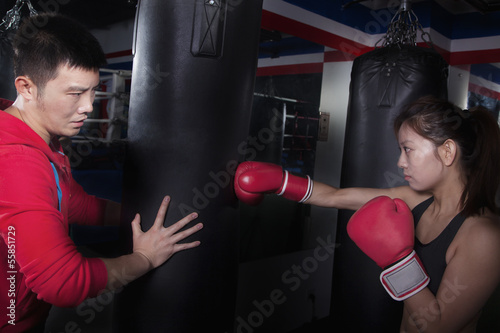 Boxing couch holding the punching bag and training a female student