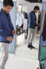 Young man trying on jacket at fashion store