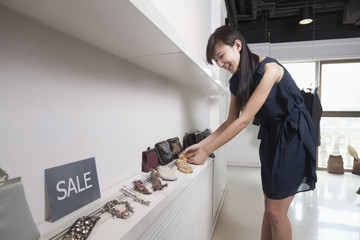 Young woman shopping for accessories at store