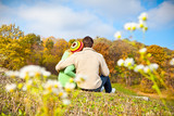 Couple sitting on a hill and looking at the autumn landscape.