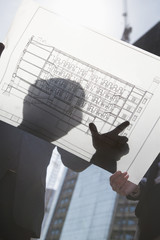 Two architects looking at blueprint on construction site