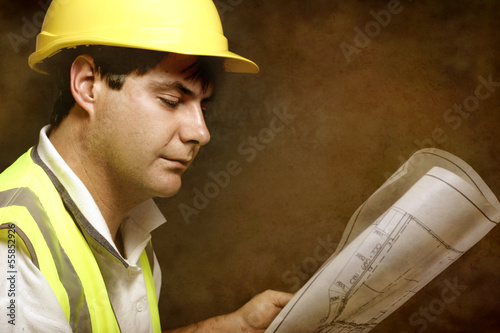 Male builder site foreman reading architectural industrial plans