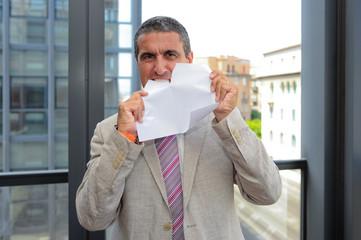 Uomo d'affari che strappa un foglio