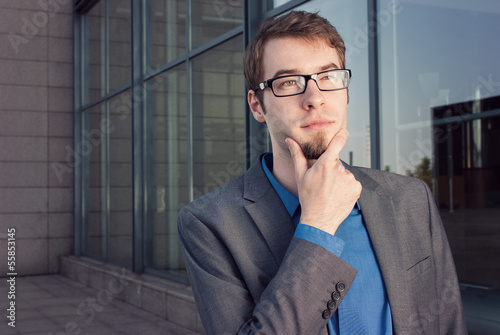 serious young businessman with arms crossed