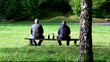Two men with a bottle in the park on a bench