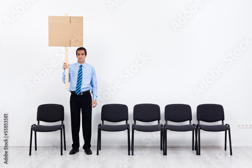 Lonely protesting businessman or employee holding placard