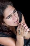 Dramatic portrait of an hispanic woman praying