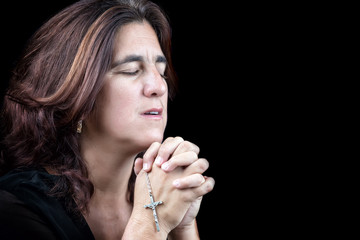 Portrait of an hispanic woman praying isolated on black