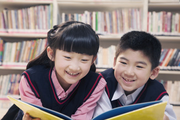 School children reading book a in the library