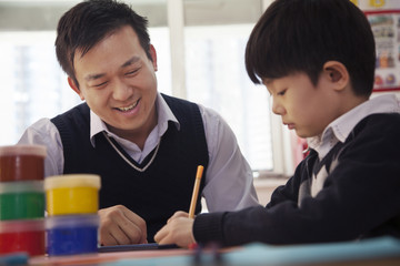 Teacher helping schoolboy with arts and crafts, Beijing