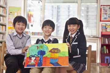 Portrait of three students with a painting