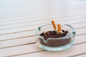 Ashtray with lit cigarette on a wooden table