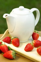 Jug with tea or coffee and strawberries.